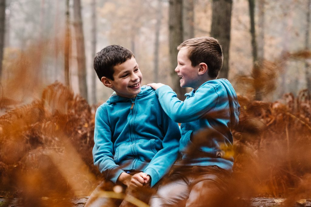 2 brothers sitting on a log in the woods, laughing