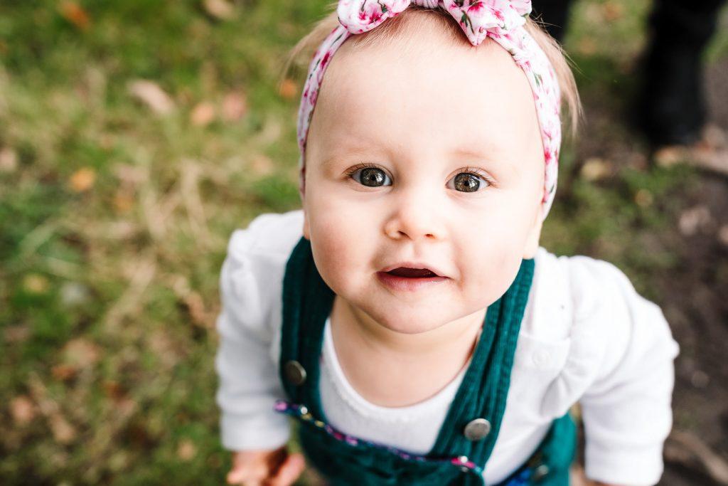 1 year old girl looking up at the camera