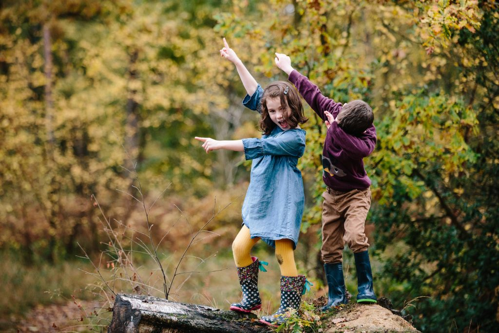boy and girl dabbing as they stand on a log. Photographing children naturally