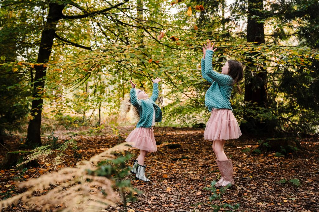 2 sisters throwing autumn leaves in the air