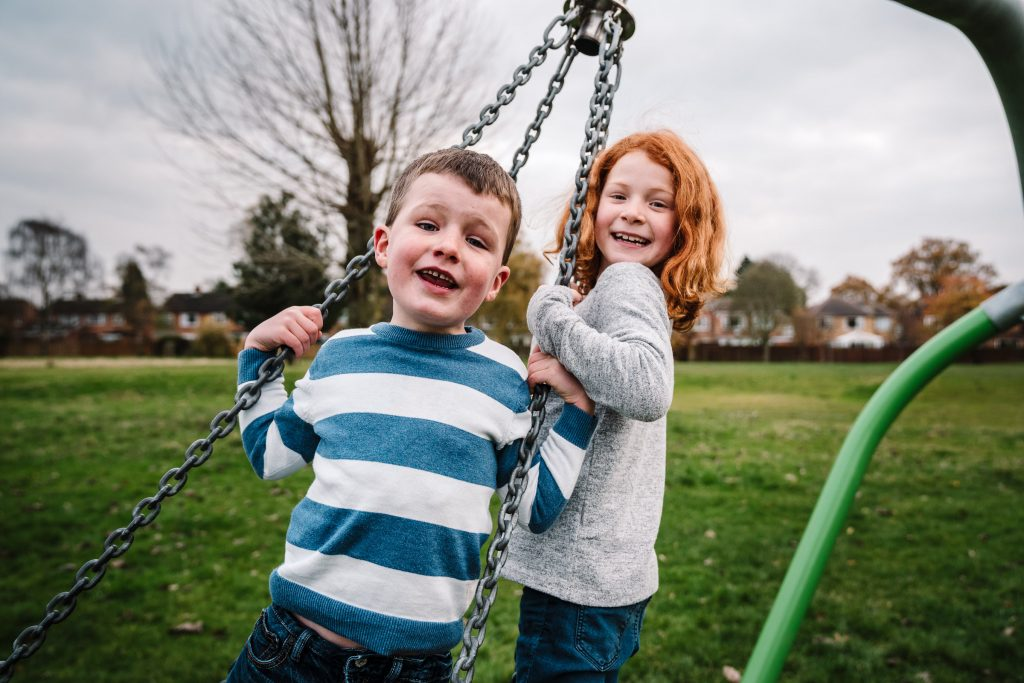 photographing children playing brother and sister swinging on a swing together