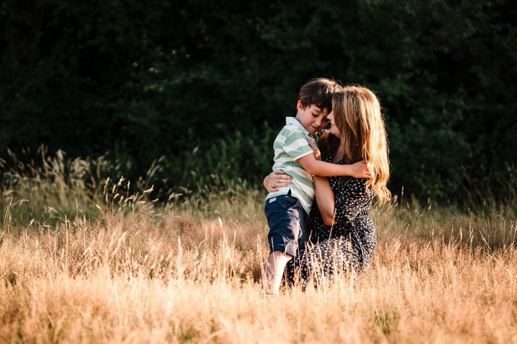 Mum and son cuddling in long grass on a photoshoot in Warwickshire