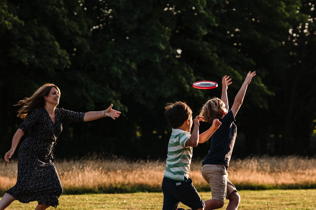 a family playing frisbee on a family shoot in Leamington Spa.  Photoshoot fun in Warwickshire
