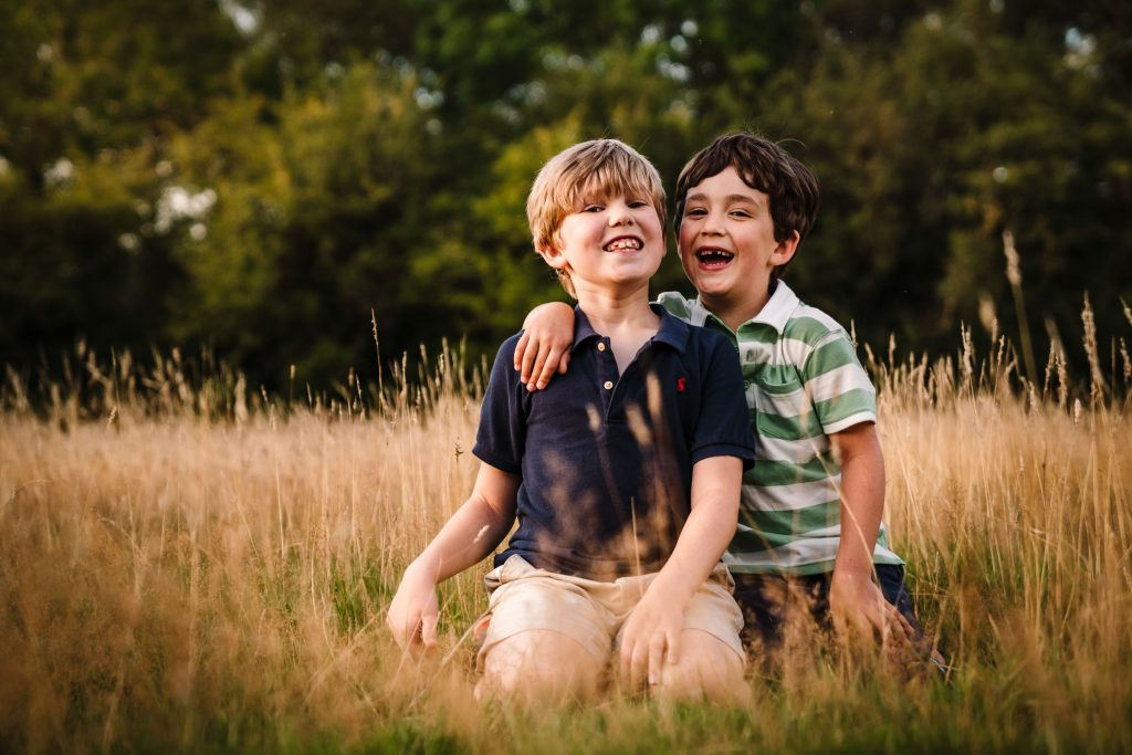 2 boys smiling and sitting in grass on a family photoshoot in Warwickshire