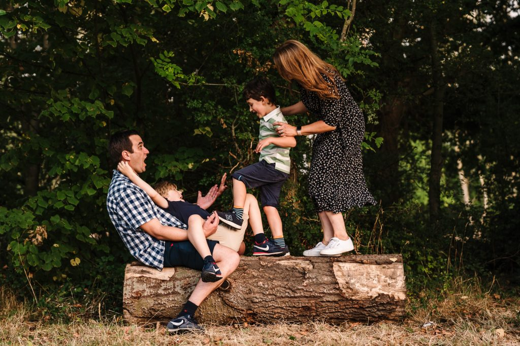 Family playing around on a log in Newbold Comyn, family photography in Warwickshire