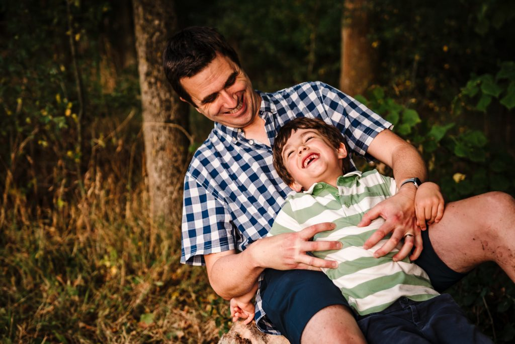 Dad tickling his son, the boy laughing