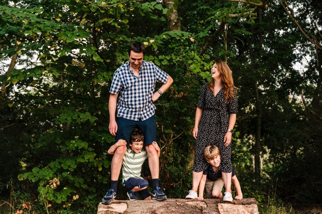A family standing on a log, the two boys peeping through their parents legs
