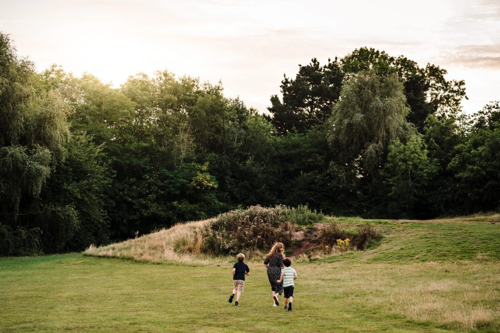 Mum and her two sons running across a park in Leamington.Family photography, Warwickshire