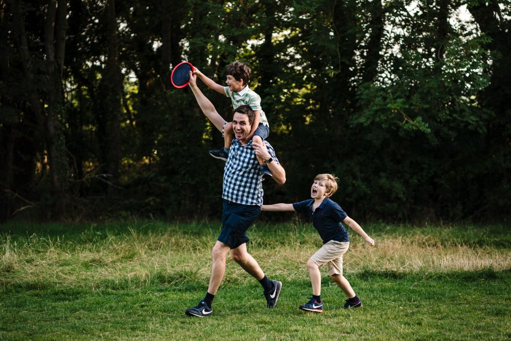 Dad and two sons playing frisbee during family photoshoot
