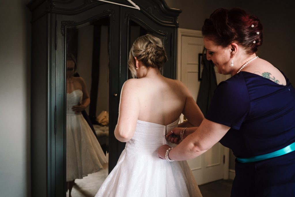 bridesmaid helping bride into her wedding dress