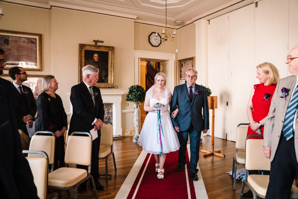 bride and her dad walking down the aisle at stratford town hall