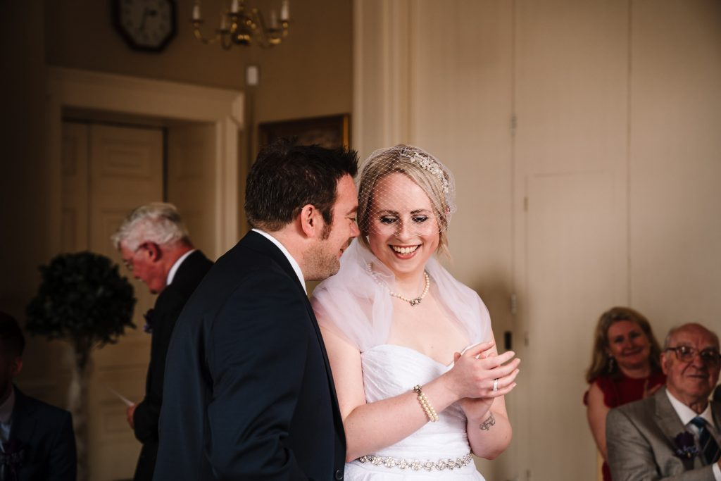 groom whispering to bride during their wedding ceremony in stratford town hall