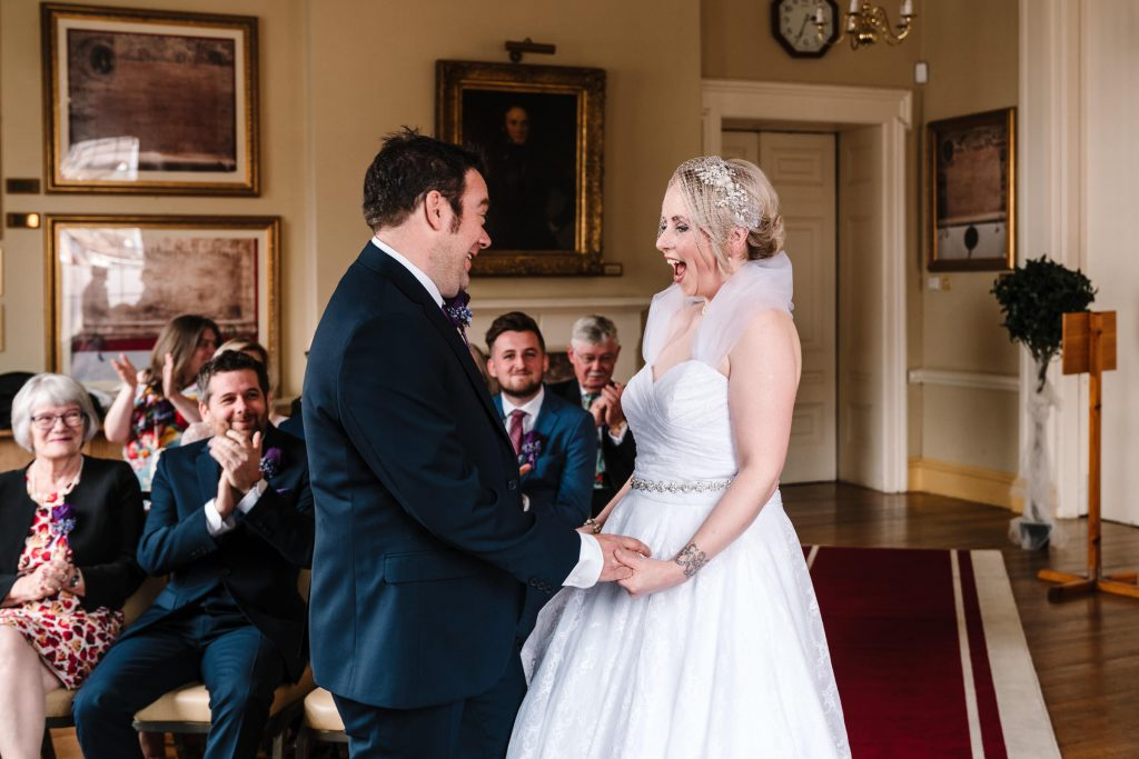 bride and groom laughing just after their first kiss when married