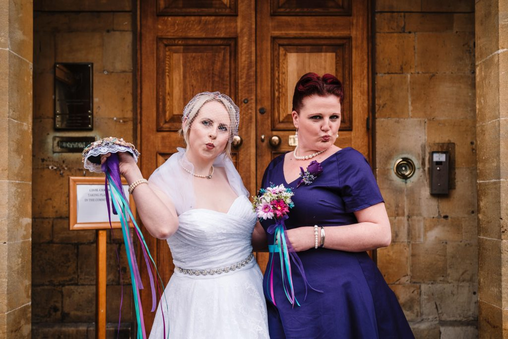 bride and bridesmaid posing for a photograph outside stratford Town hall