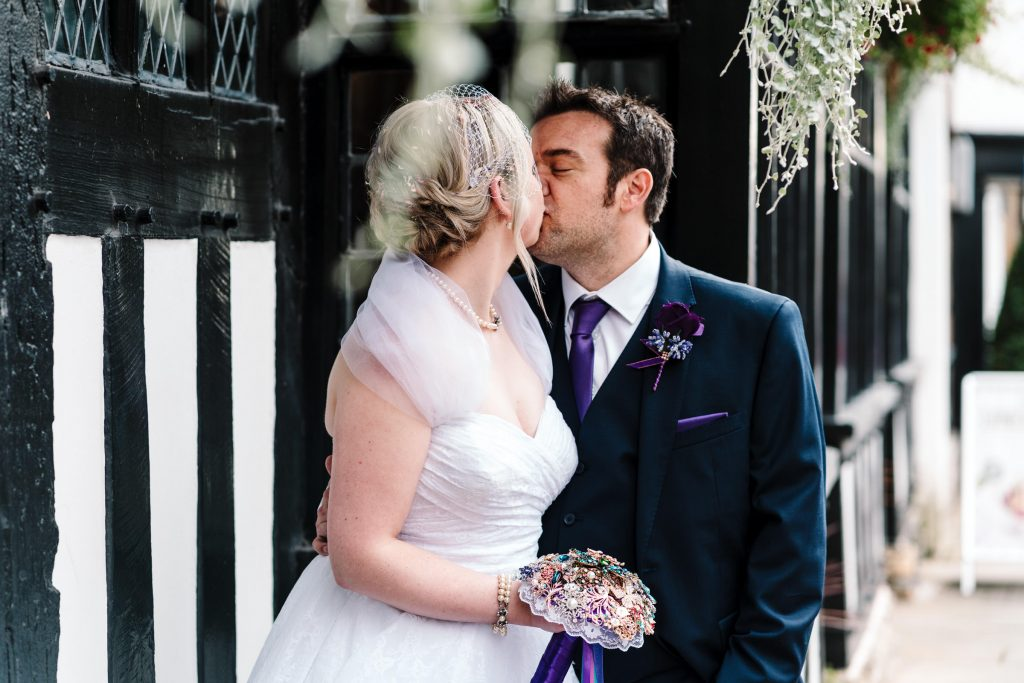 bride and groom kissing standing by a black and white building in Stratford