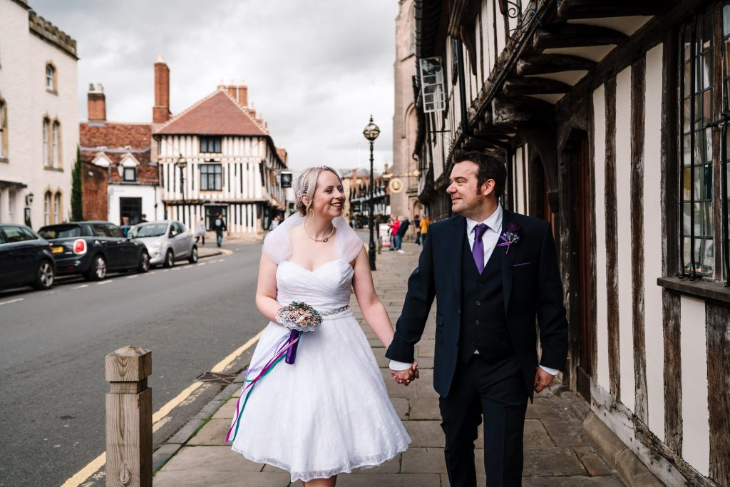 bride and groom walking down the road in stratford upon avon
