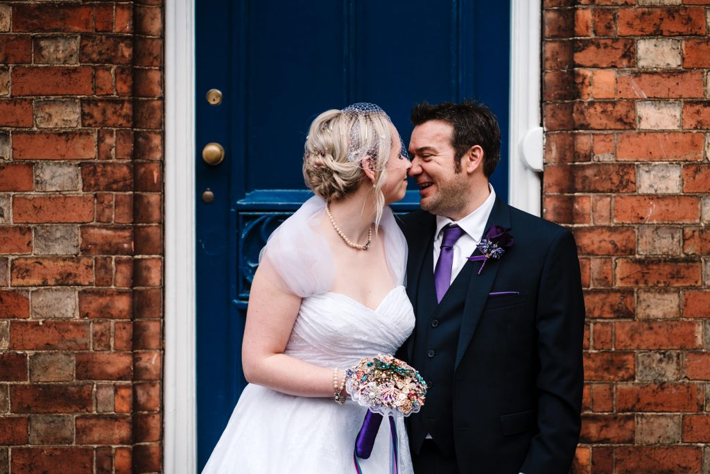 bride and groom in front of a blue front door in stratford