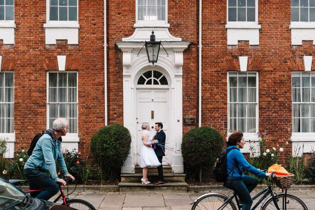 bride and groom cuddling on a doorstep in Stratford as cyclists go by