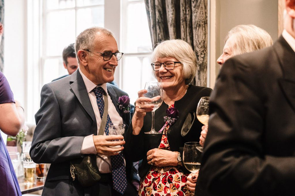 guests drinking champagne and laughing during wedding reception