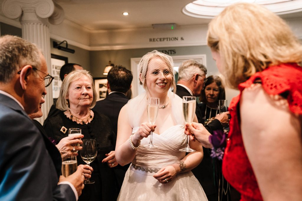 bride drinking champagne with her guests at wedding in stratford upon avon