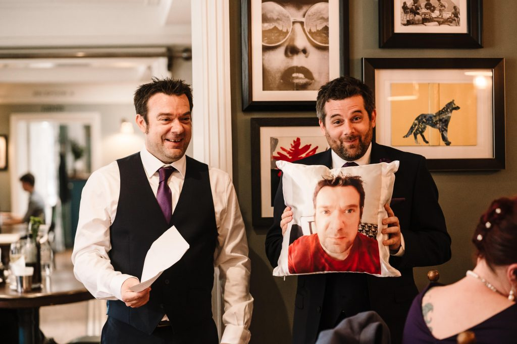 best man holding up funny present from the groom during wedding speech