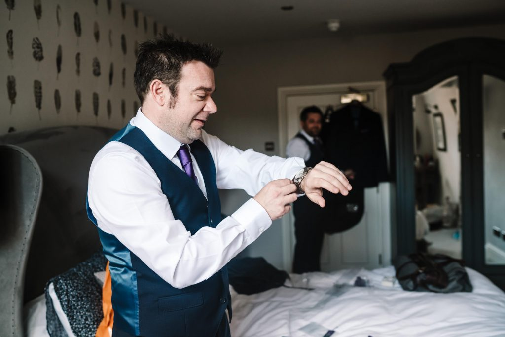 groom looking at his watch as he gets ready for his wedding