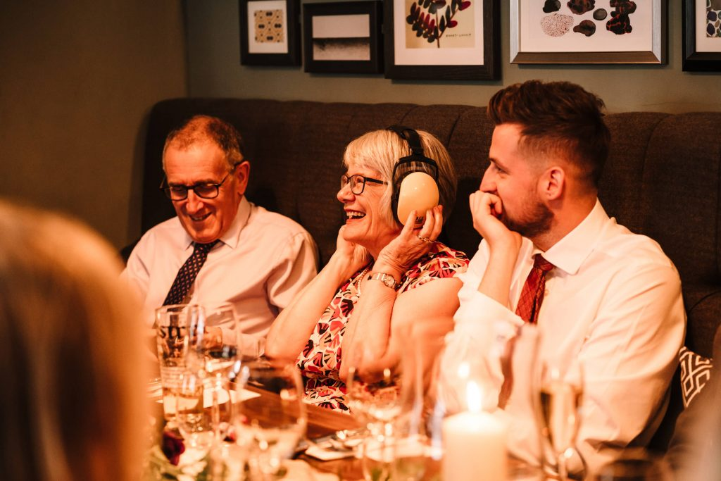 mother of the groom wearing ear muffs during wedding speech