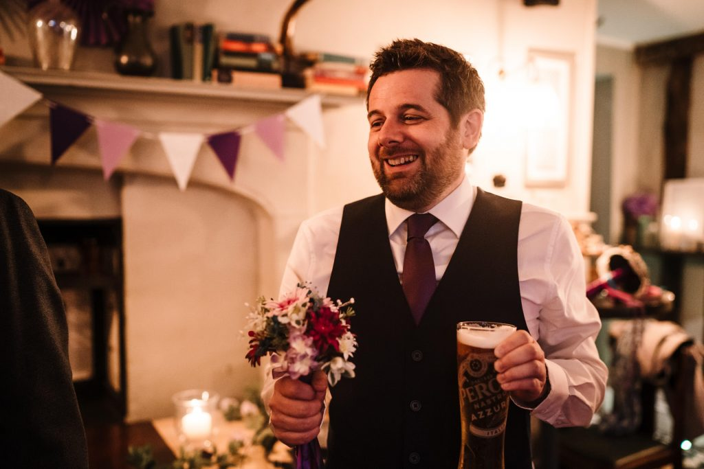 best man holding a pint of beer and flowers