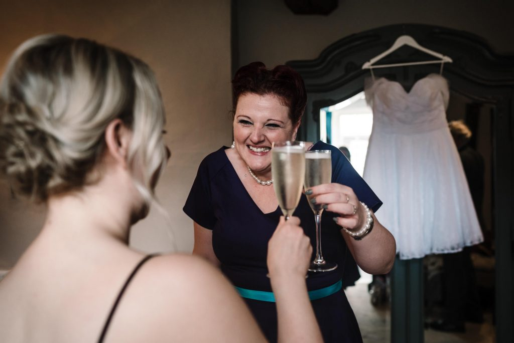 bride and bridesmaid doing cheers with champagne