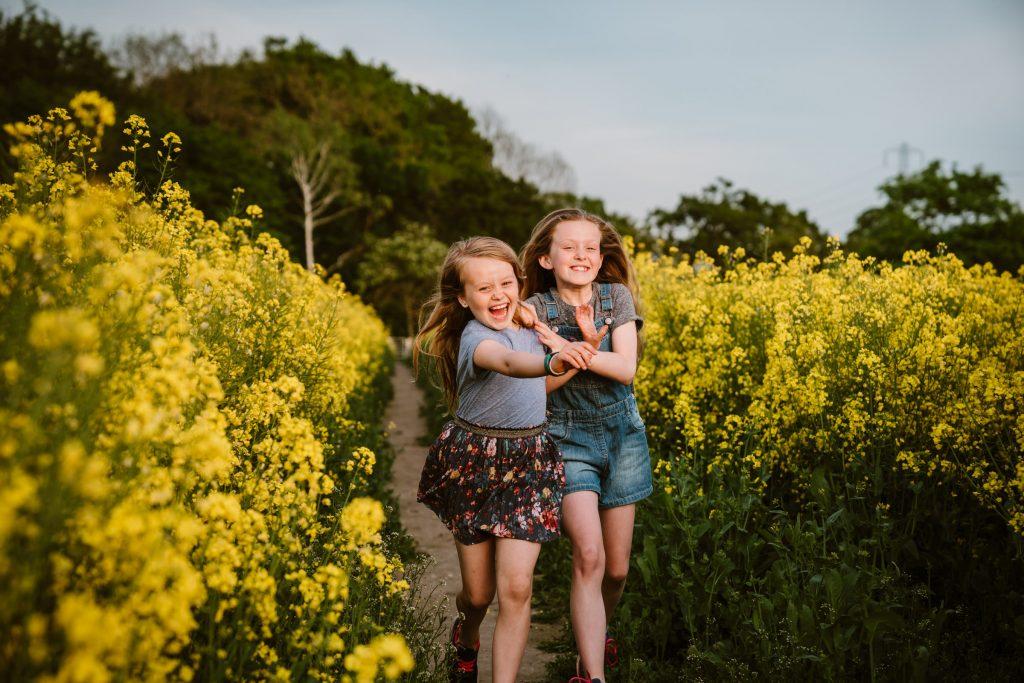 girls running through rapeseed field during family photoshoot