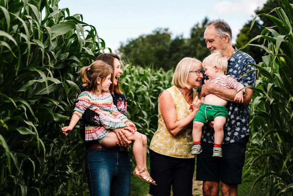 Family standing in a field of maize during photoshoot