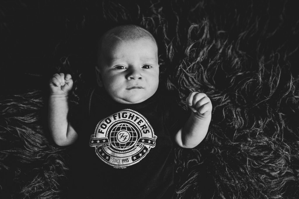 black and white image of baby with a foo fighters vest on