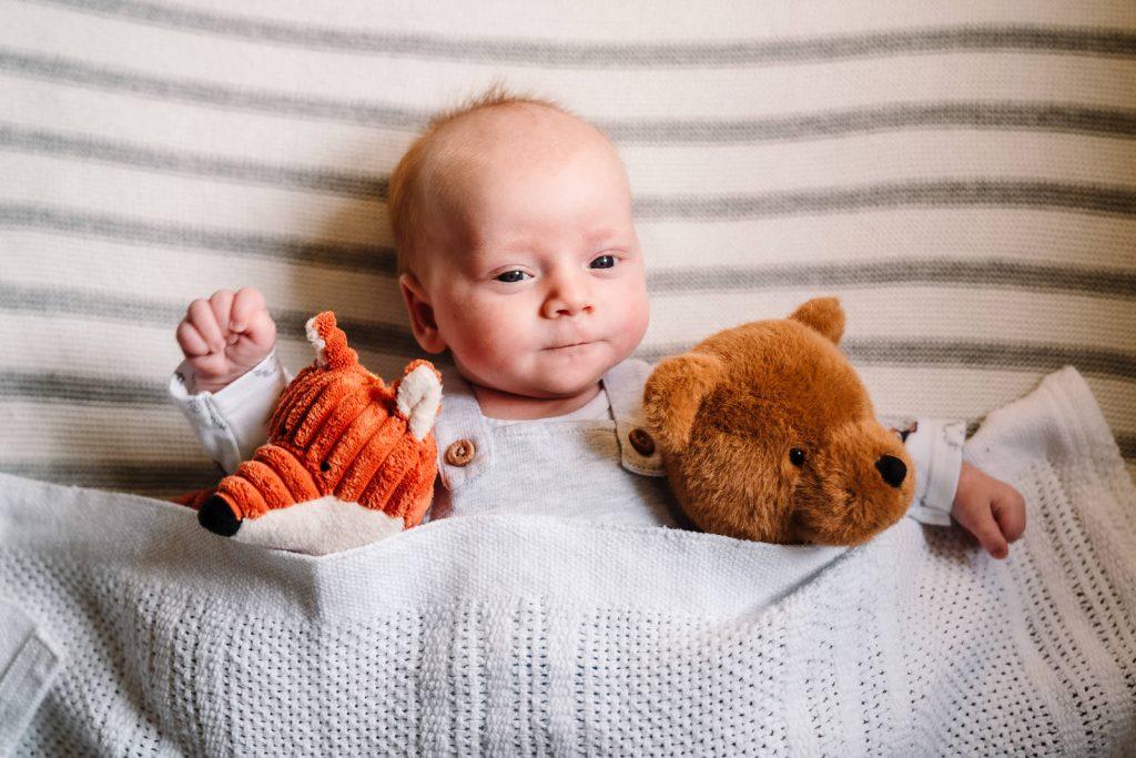 baby cuddling his teddies in newborn photoshoot