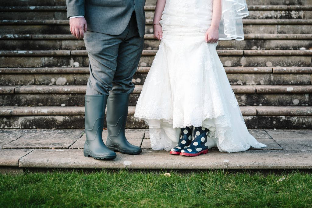 bride and groom in wellies with rain on wedding day