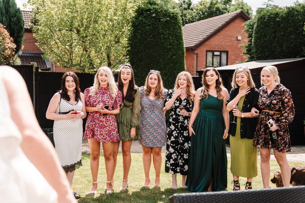 Bride revealing wedding dress to friends
